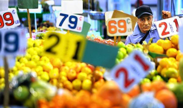 """A shopper examines produce at grand Central Market. Adele Yellin, head of the company that runs Grand Central, says she wants to blend the old and new. But a vendor says: """"These people are not going to pay $10 for a pound of meat."""""""