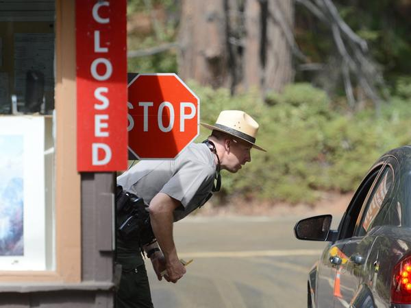 Park ranger Jeff Gardner informs visitors of the closure of Yosemite National Park due to the government shutdown Tuesday, October 1, 2013. Day visitors were allowed to pass through Yosemite but were instructed not to stop or use any facilities. (Craig Kohlruss/Fresno Bee/MCT)
