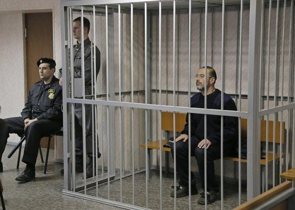 Greenpeace activist Dima Litvinov sits in a cell in a courtroom in Murmansk, Russia.