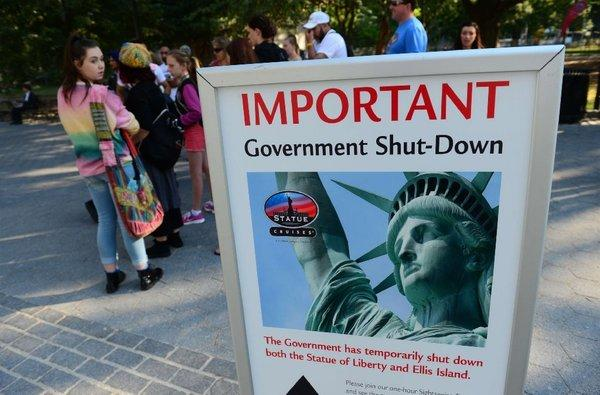 Tourists walk by a sign announcing that the Statue of Liberty is closed due to a federal government shutdown.