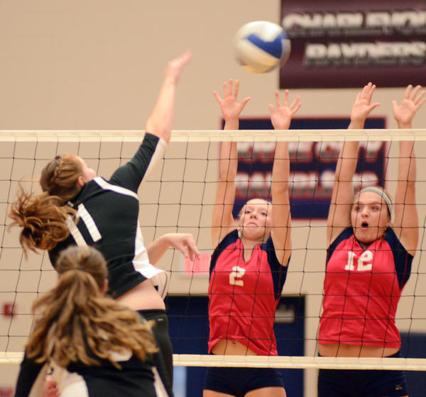 East Jordan senior Paige Poindexter (left) sends a shot past the outsretched block of Boyne Citys Megan Rushlow (middle) and Mallory Karaszewki during a Lake Michigan Conference match Tuesday at the Boyne City High School gym. The Ramblers defeated the Red Devils in four sets.