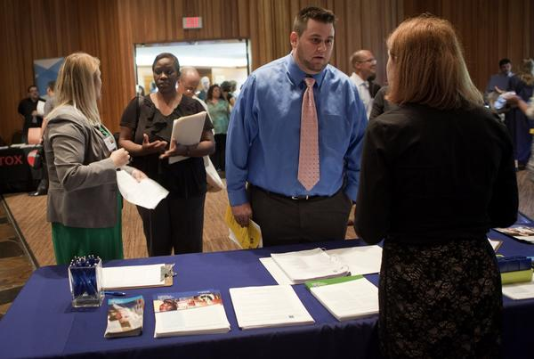 A job seeker speaks to a representative at the annual Maximum Connections job fair in Portland, Ore.