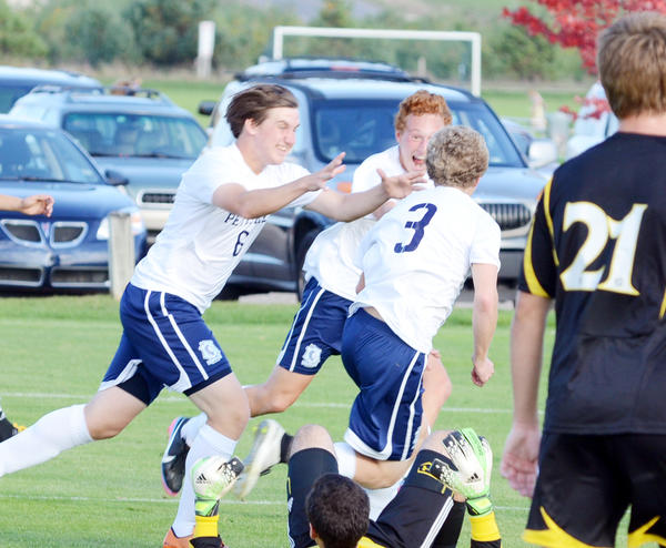 Petoskey junior Ben Godfrey (from left) junior Cooper Carpenter and senior Austin Redes celebrate Redes first half goal against Traverse City Central Tuesday at the Click Road Soccer Complex. The Northmen defeated the Trojans, 3-0, in the Big North Conference contest.