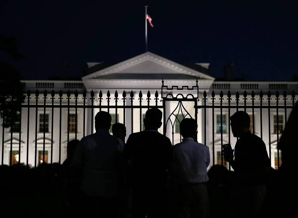 People stand in front of the White House on Monday evening, a few hours before the much of the federal government shut down midnight Tuesday.