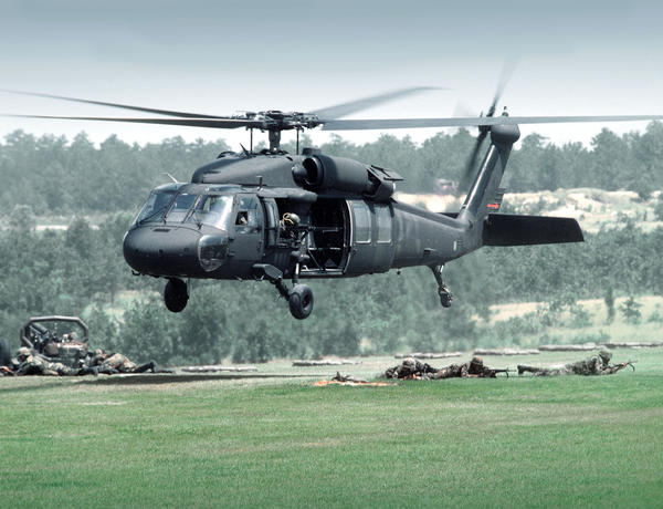 A Black Hawk departs the landing zone over troops and field guns.
