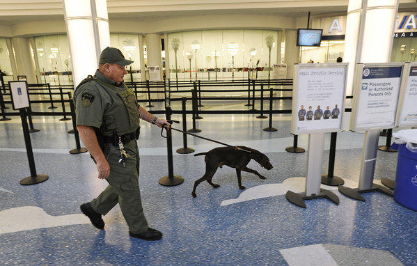 Jacksonville International Airport police Officer Tim Hodges searches a passenger area with a bomb-sniffing dog after a man allegedly told security screeners that he had a bomb in his backpack. But they only found a luggage scale with a microchip inside, along with a remote control device he called a detonator.