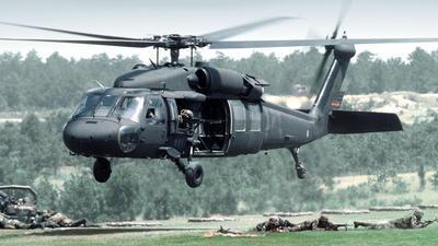 Un Black Hawk se aleja de la zona de aterrizaje sobre las tropas y armas en el campo.