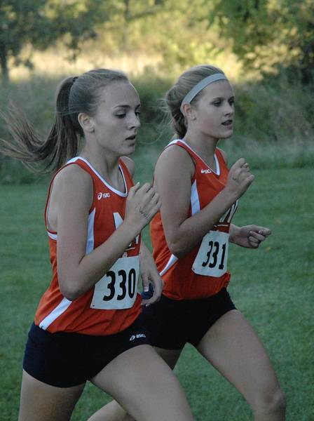 Naperville North sophomores Ella Guppy and Emory Griffin compete at the Naperville Invitational on Friday.
