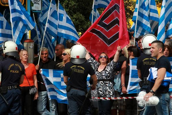 Supporters of the ultra-right Greek political party Golden Dawn wave the national flag and the swastika-like party banner outside an Athens courthouse as they await the release on bail of party leaders accused of organizing a criminal enterprise.