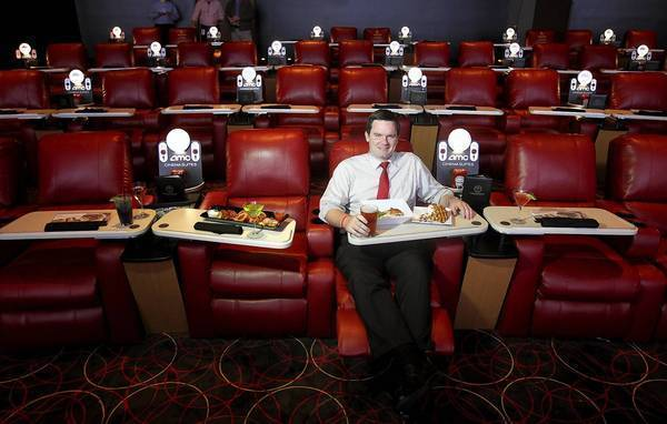 AMC spokesman Ryan Noonan sits in an AMC theater in Marina del Rey that allows patrons to order food and drink from their seats. AMC has remodeled another theater in West Hills with similar seating, but no dining services.
