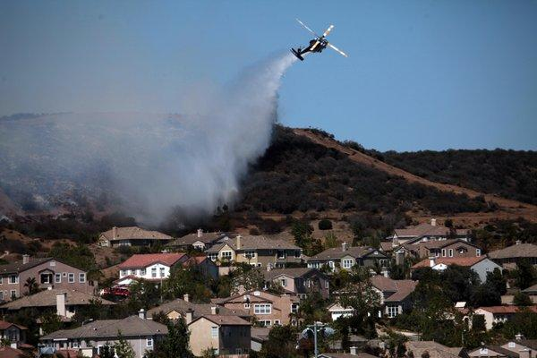 A helicopter douses a fire near Camarillo Springs that was fueled by Santa Ana winds and warm temperatures.