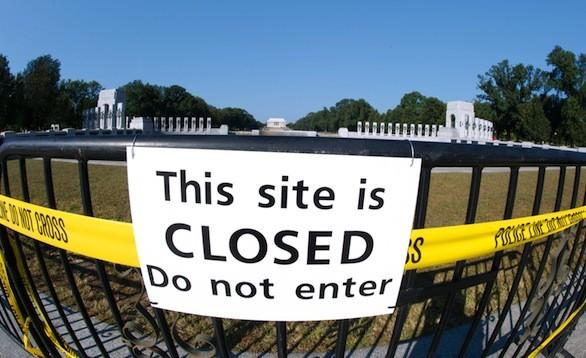 A closure sign Wednesday hangs at the front of the World War II Memorial in Washington, D.C. The Smithsonian museums as well as memorials and monuments have been affected by the government shutdown.