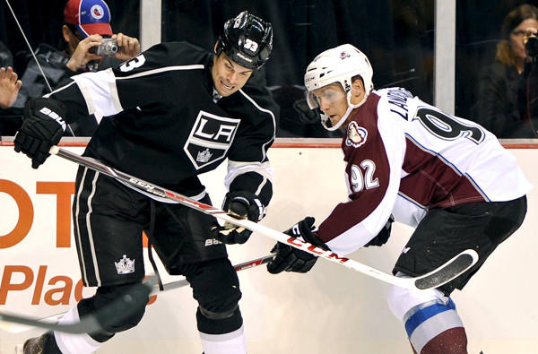 Kings defenseman Willie Mitchell, left, battles Avalanche left wing Gabriel Landeskog for the puck during a preseason game.