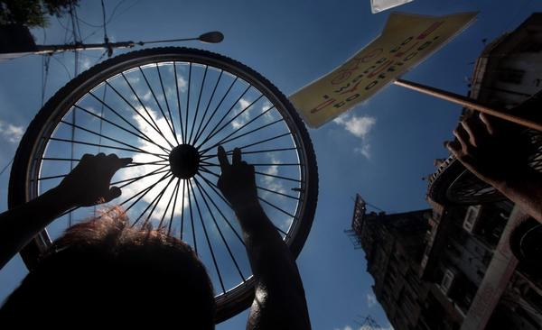 Bicyclists in Calcutta hold up a spoked wheel in a Wednesday protest against the city's ban on riding bikes on 174 city thoroughfares.