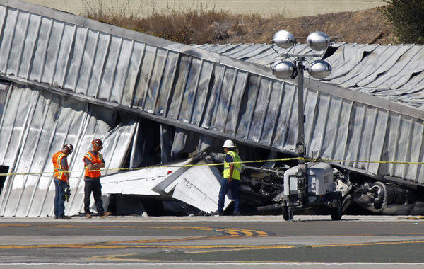 Investigators stand near the tail section of a twin engine Cessena jet plane outside an aircraft hangar at Santa Monica Airport on Sept. 30.