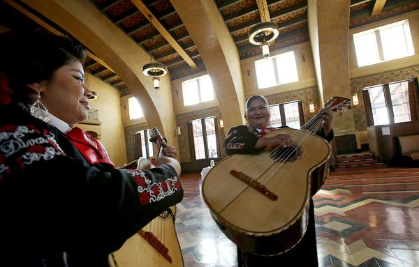 Daniela Gutierrez and Wendy Alarcon, members of Mariachi Diva, warm up before performing at the launch of Covered California, the state's Affordable Care Act marketplace, at Union Station in Los Angeles on Tuesday.