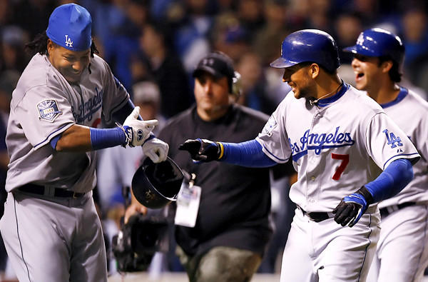 Dodgers first baseman James Loney (7) celebrates with teammate Manny Ramirez after hitting a grand slam against the Chicago Cubs in Game 1 of the National League division series at Wrigley Field.
