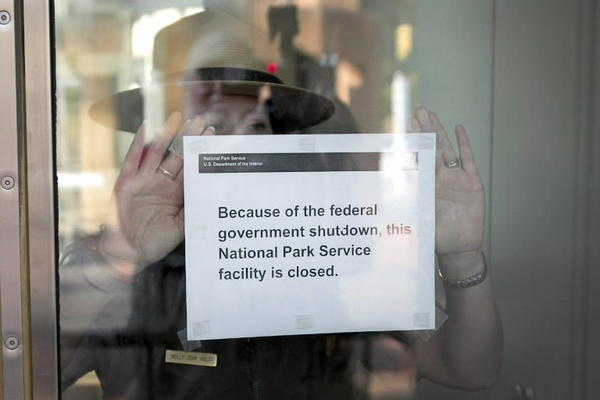 Holly Jean Holst, park ranger at Independence National Historical Park, places a sign on the door of the Liberty Bell pavilion informing visitors that the historic site is closed due to the government shutdown on October 2, 2013, in Philadelphia.