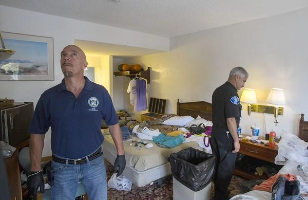 Costa Mesa Code Enforcement Officer Mike Brumbaugh, left, and Fred Seguin, the deputy chief with the Costa Mesa Fire Department, inspect a room for code violations at the Alibaba Motel in Costa Mesa on Wednesday.