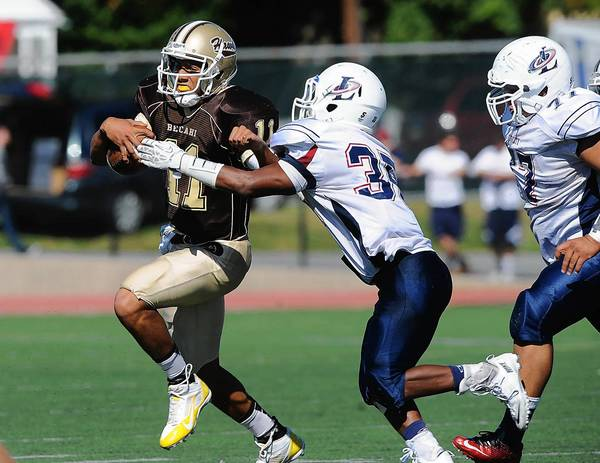 Bethlehem Catholic's Julian Spigner (left) is chased out of the pocket by Liberty's Ryan Lawrence (right) during their Lehigh Valley Conference high school football game Saturday, September 28, 2013.