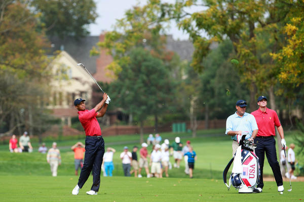 Tiger Woods plays to the green of the 14th hole as Steve Sticker watches during a practice round prior to the start of The Presidents Cup.