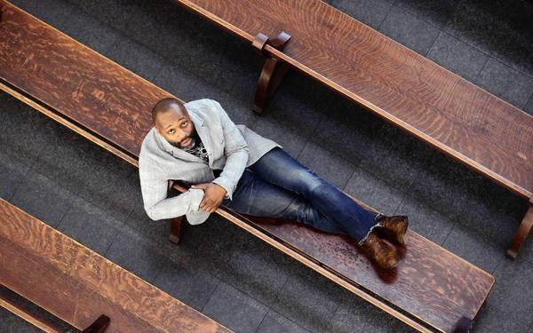 Artist Theaster Gates sits with his large-scale installation, 13th Ballad, at Chicago's Museum of Contemporary Art earlier this year.