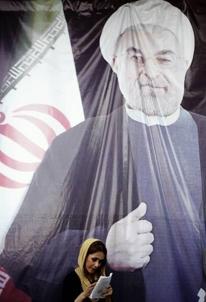 An Iranian woman checks her mobile phone as she stands in front of a giant portrait of eventual President Hasan Rouhani outside his campaign headquarters in downtown Tehran in June.