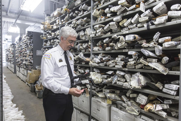 Michael Mealer, commander of evidence recoverey for the Chicago police department holding a firearm at their seized gun vault on the west side of Chicago which stores 80,000 firearms on September 30, 2013. ( Lenny Gilmore/ RedEye )