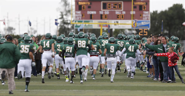 Presentation College football team members run through a tunnel of fans as they take the field for Saturday's game against Waldorf College at Swisher Field.