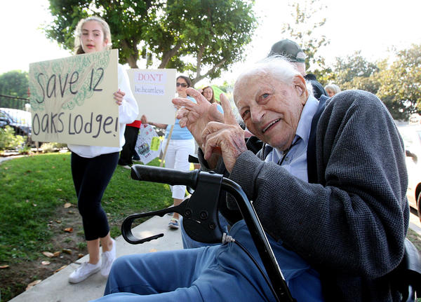 12 Oaks Lodge resident Dean Deardorf, 96, happily moves his hands to the beat of the chant yelled by a long line of protesters marching in front of be.group in Glendale. Locals protested the closing of Twelve Oaks Lodge in La Crescenta, where Deardorf lives, on Wednesday, Oct. 2, 2013. Nearly 125 people protested in front of the Glendale business.