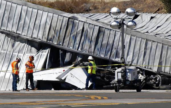 Investigators stand near the tail of a twin-engine Cessna jet that crashed into a hangar on landing Sunday night at Santa Monica Airport. Two people were killed.