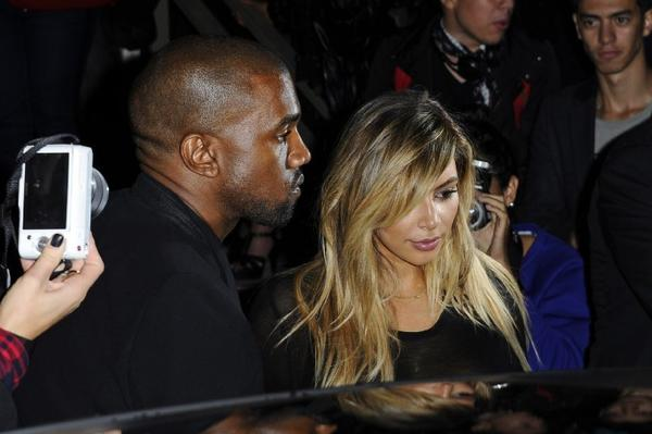Kanye West, left, and Kim Kardashian leave after attending a Givenchy show at Paris Fashion Week.