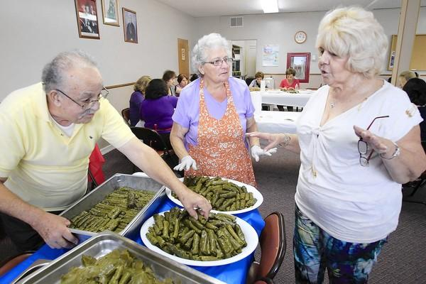 Claudette Mekalian, right, chairwoman of the Ladies Society, speaks to Alicia Setyan, center, and her husband Karbet as they, and dozens of other volunteers prepare yalanchi, stuffed grape leaves, at St. Mary Armenian Church in Costa Mesa on Wednesday. They plan to make more than 3,000 yalanchi for this year's Armenian Festival.