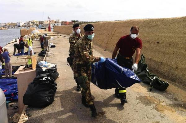 The body of a drowned passenger who was aboard a boat loaded with African migrants is brought ashore on the Italian island of Lampedusa.