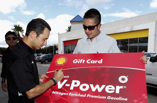 IndyCar driver Helio Castroneves surprises fans with free fuel and prizes during an event Thursday promoting the Grand Prix of Houston.