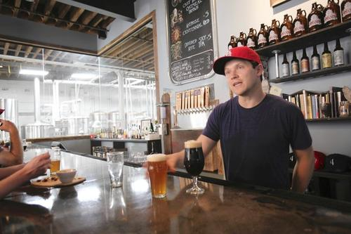 A bartender at 4 Paws Brewing has his baseball allegiance in order.