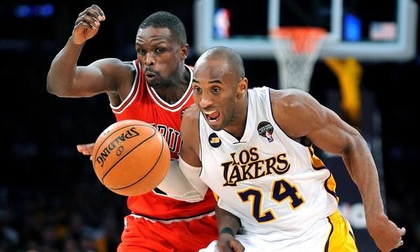 Lakers guard Kobe Bryant, right, drives ahead of Chicago's Luol Deng during a game in March. The Lakers are reluctant to provide an exact timetable on Bryant's return from his Achilles injury.