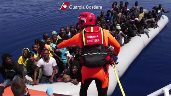 An Italian coast guardsman oversees the Aug. 8 arrival of a refugee-packed boat off the island of Lampedusa, where about 300 may have died Thursday when another overloaded fishing boat caught fire and capsized half a mile offshore.
