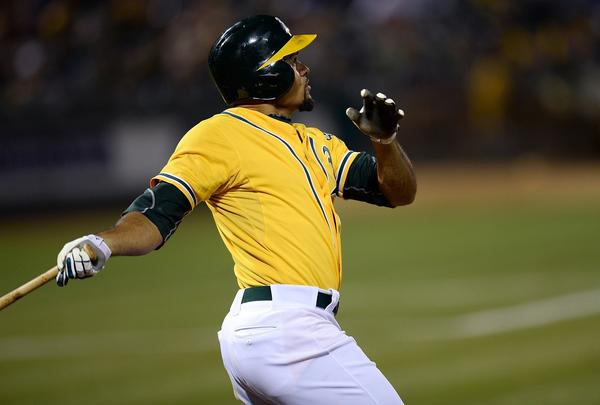 Coco Crisp swings and watches the flight of his ball as he hits a two-run homer in the bottom of the eighth inning against the Twins.