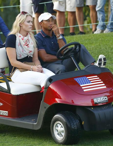 Tiger Woods sits in a golf cart with his girlfriend Lindsey Vonn as they watch play during the opening four-ball matches for the 2013 Presidents Cup.