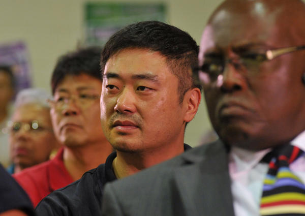 Jay Chung, center, owner of the Charles Village Schnapp Shop, listens to comments during a public hearing at the Towanda Community Center about the proposal to close some liquor stores as part of the city's new zoning plan. Chung opposes the changes which he says will threaten his business.