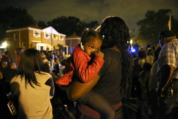 Erica Sykes holds daughter Taelynn Sykes, 3, during a meeting Wednesday with CAPS members and residents near the Far South Side's Merrill Playground Park, one night after a shooting wounded three teenagers.