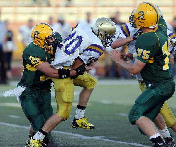 Aberdeen Roncalli's Lucas Lorenz, left, wraps up Flandreau's Jace Christiansen (10) as the Cavaliers' Zach Andera, right, gets blocked by Flandreau's Tim Parsley during a game this season at Swisher Field.