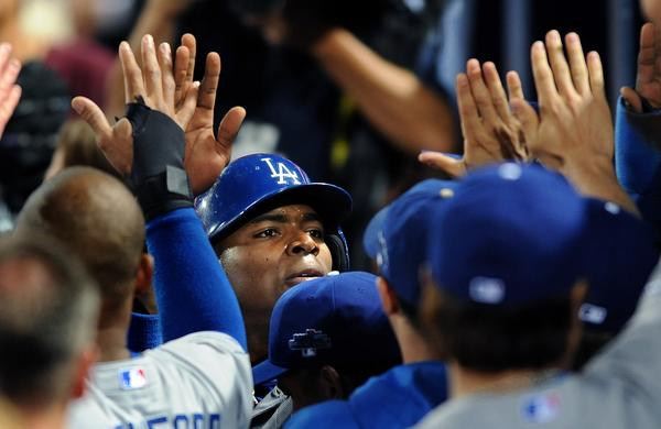 Dodgers right fielder Yasiel Puig is congratulated by his teammates after scoring in the second inning of the Dodgers' 6-1 win over the Atlanta Braves in Game 1 of the National League division series Thursday.