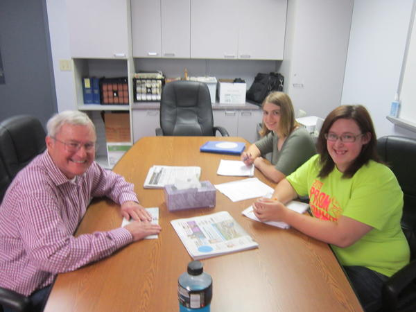 Robert Haines (from left) sits down for an interview with Alanson public communications students, seniors Ashleigh Ross and Sierra Oliver. Haines returns to Northern Michigan during the summer season, but resides in Houston, Texas, during the winter months. He shared with the student reporters his career path. Haines was a stock broker for more than 40 years.