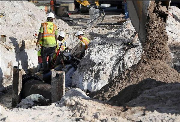 Workers continue to repair a water main break at South 28th Avenue and Van Buren Street in Hollywood on Friday, Oct. 4, 2013.