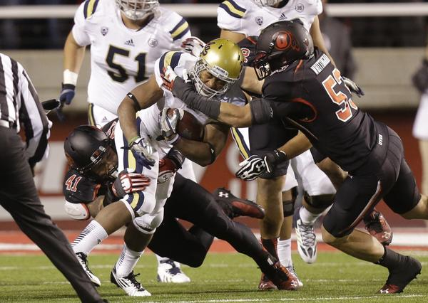 UCLA running back Jordon James carries the ball as Utah linebackers Jared Norris (41) and Jason Whittingham make a tackle in the second quarter during the Bruins' 34-27 victory Thursday night.