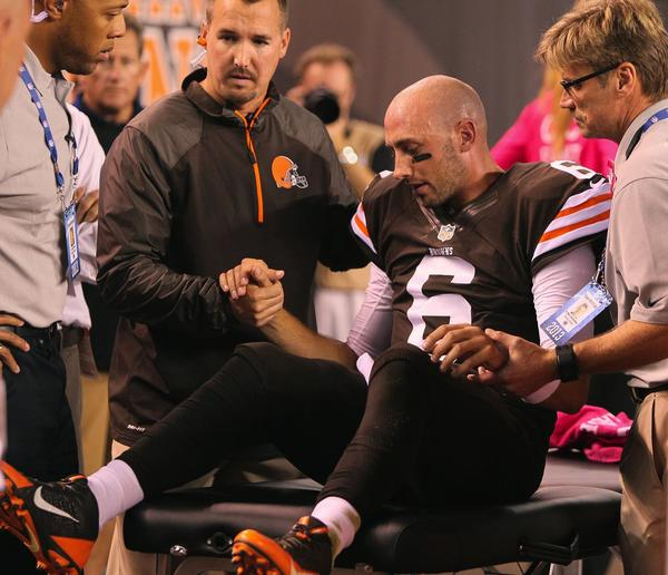 Cleveland Browns quarterback Brian Hoyer is helped up by medical staff on his way to the locker room after being injured in the first quarter against the Buffalo Bills Thursday night.