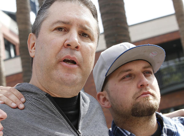Robert Preece and Robert Preece Jr., father and brother of Jonathan Denver, make a public plea for witnesses outside AT&T Park.