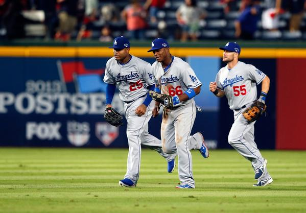 Carl Crawford, Yasiel Puig and Skip Schumaker, left to right, run to the dugout after defeating the Braves in Game 1 of the National League Division Series at Turner Field in Atlanta.